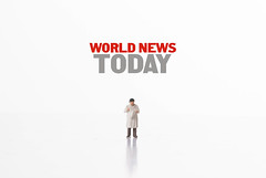 Miniature man reading newspaper and World News Today text