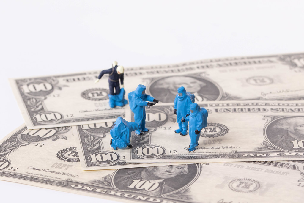 Workes in blue protective suits on Dollar banknotes