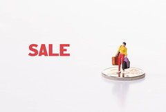 Woman standing on 2 Euro coin with Sale text