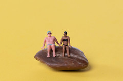 Couple in bathing suit sitting on rock
