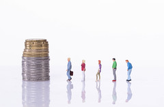 People standing in line in front of coin stack on white background
