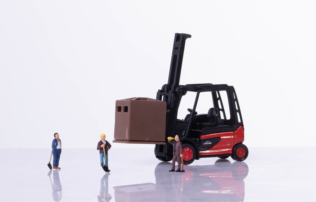 Miniature workers with forklift on white background