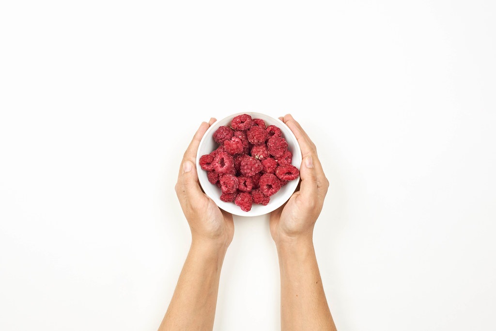Woman hands holding a bowl of freshly picked raspberries