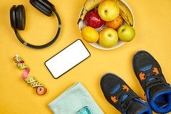 Healthy lifestyle background with fruits, headphone, measuring tape, towel, sneakers and smartphone