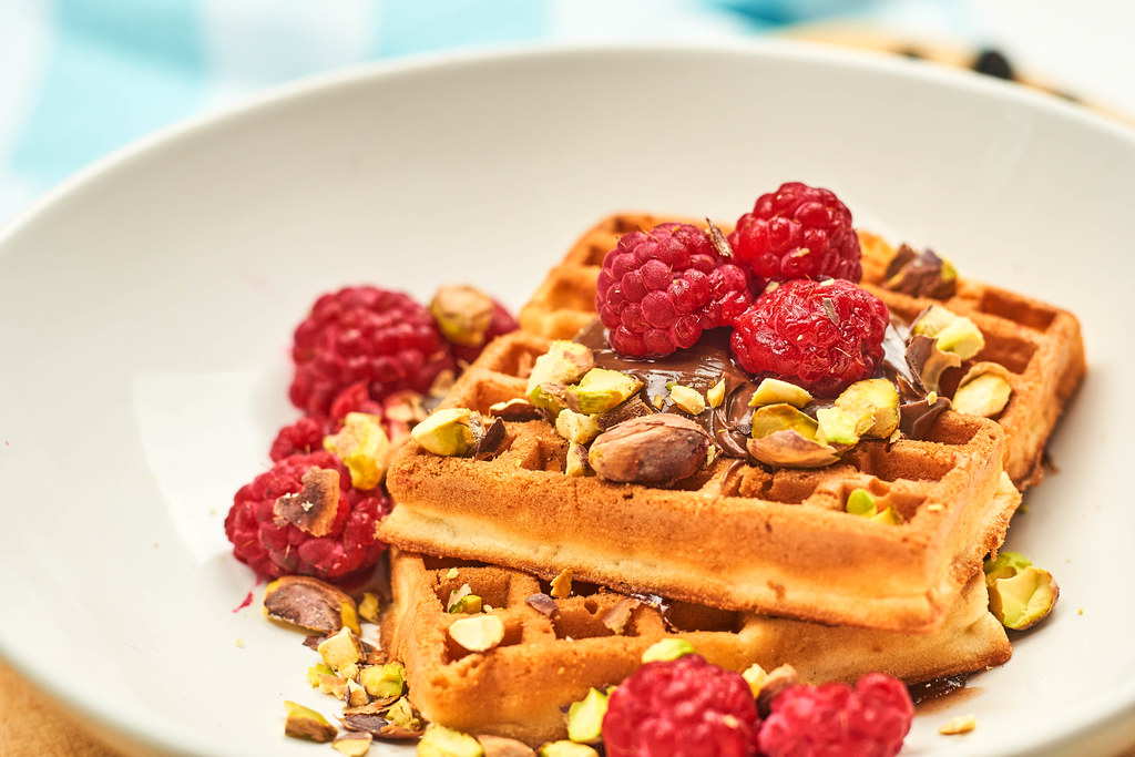 Healthy breakfast with sweet waffles covered with pista and raspberries