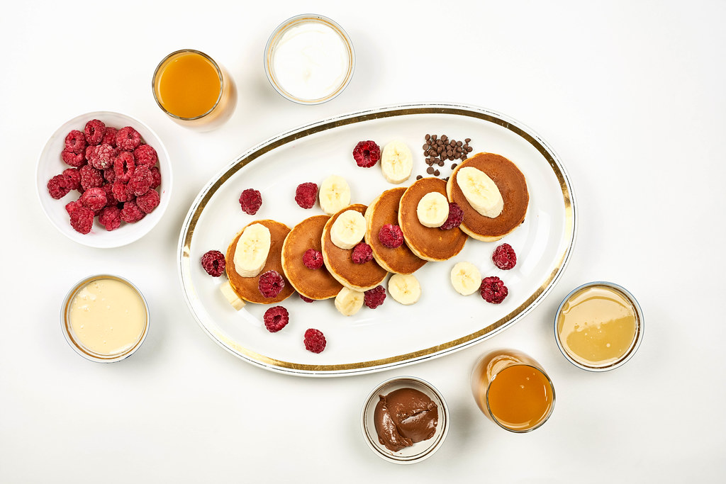 Bright breakfast table with pancakes, fruits, chocolate and honey