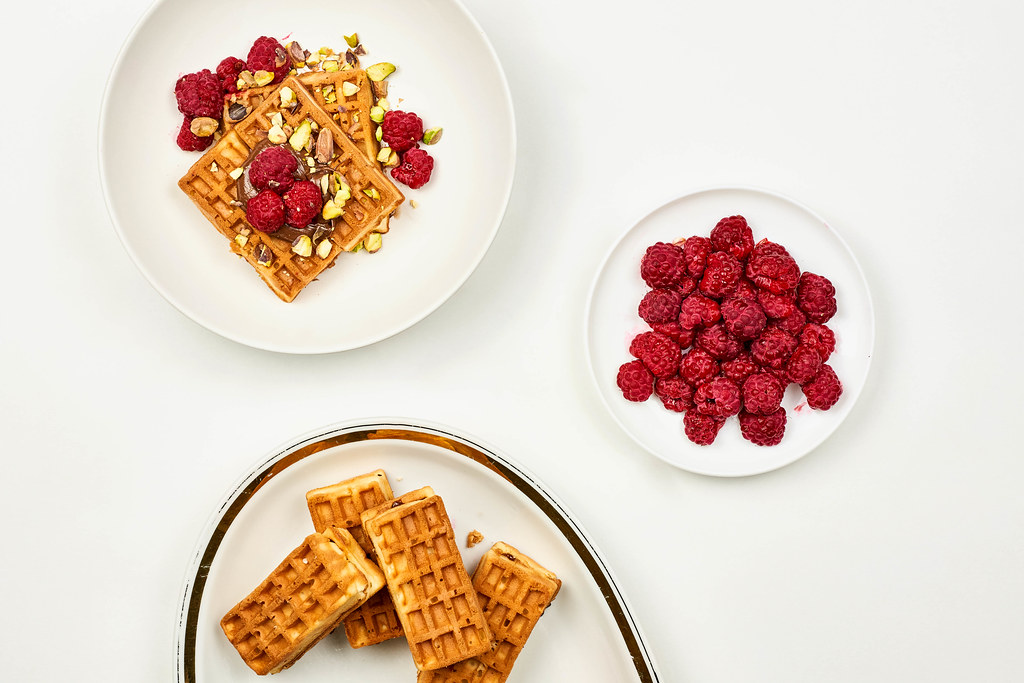 Belgian waffles with raspberries for tasty breakfast on white table