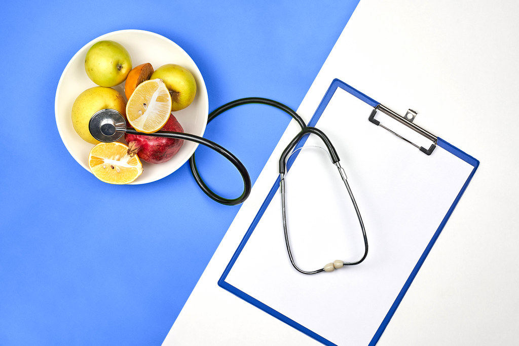 A plate of organic fruits, stethoscope and blank A4 paper on bright split-tone background