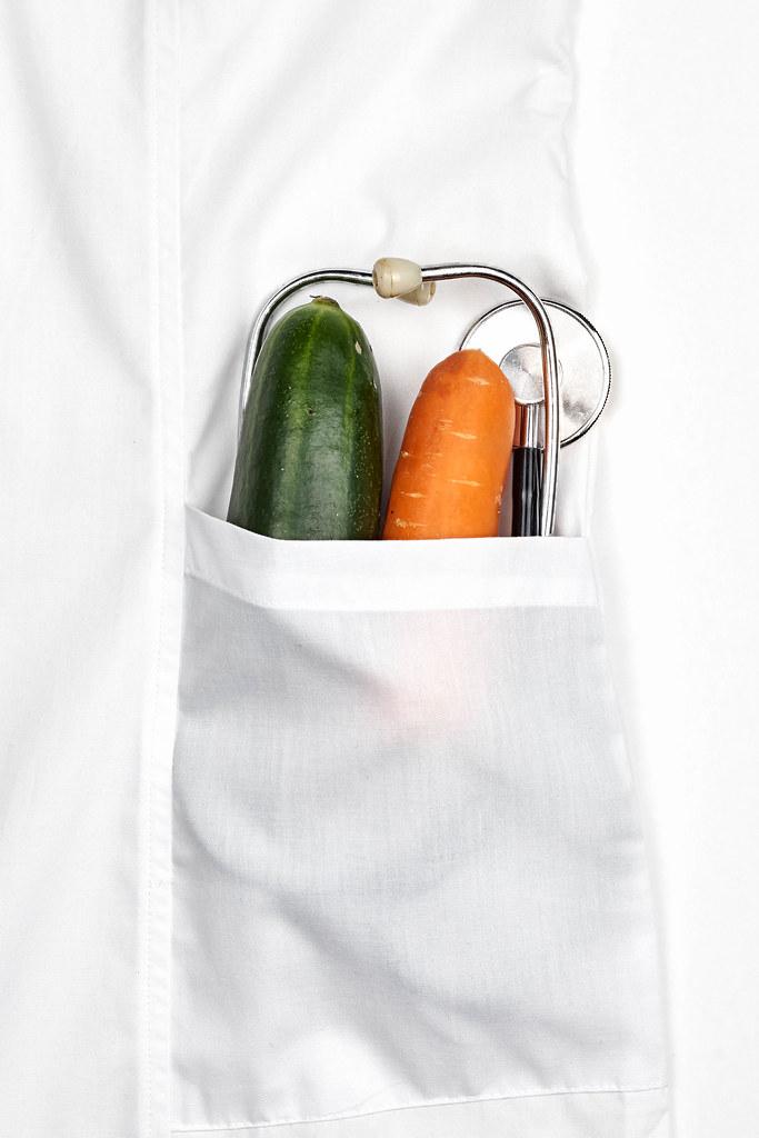 Organic ripe vegetables in pocket of white doctor's coat