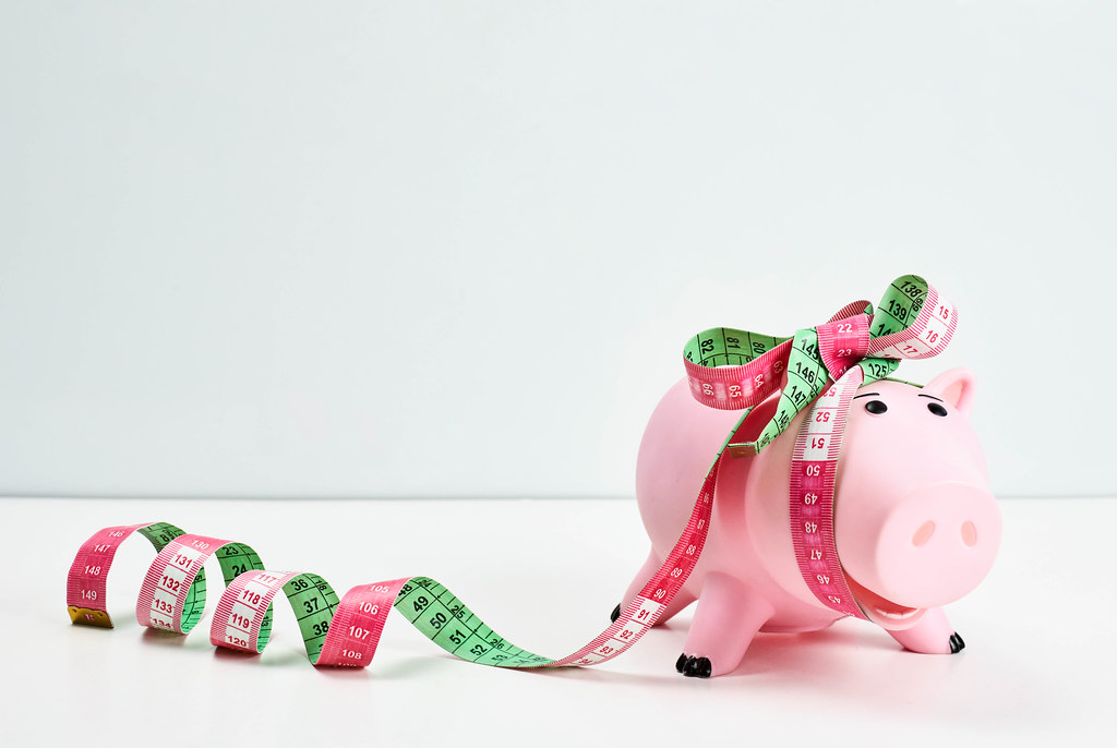 Cute piggy bank wrapped as a gift with measuring tape