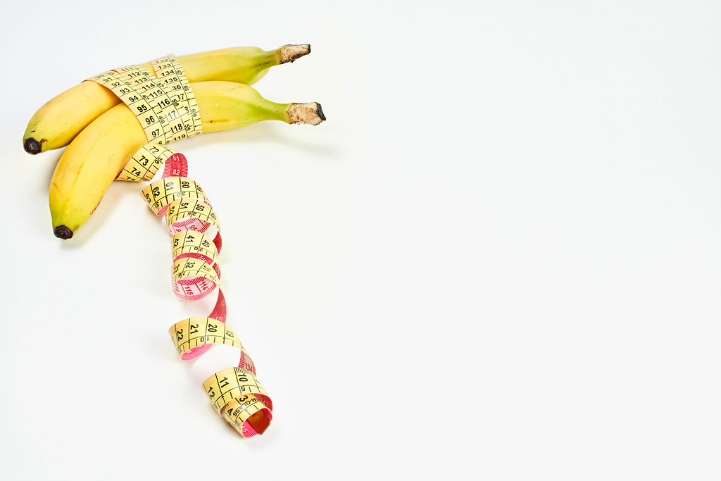 Measuring tape wrapped around bananas. Concept of penis enlargement, healthy eating, dieting and weight loss