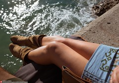 legs boots by the ocean wall