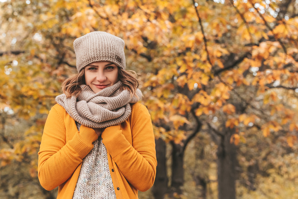 Girl in a knitted hat and scarf on a background of autumn trees