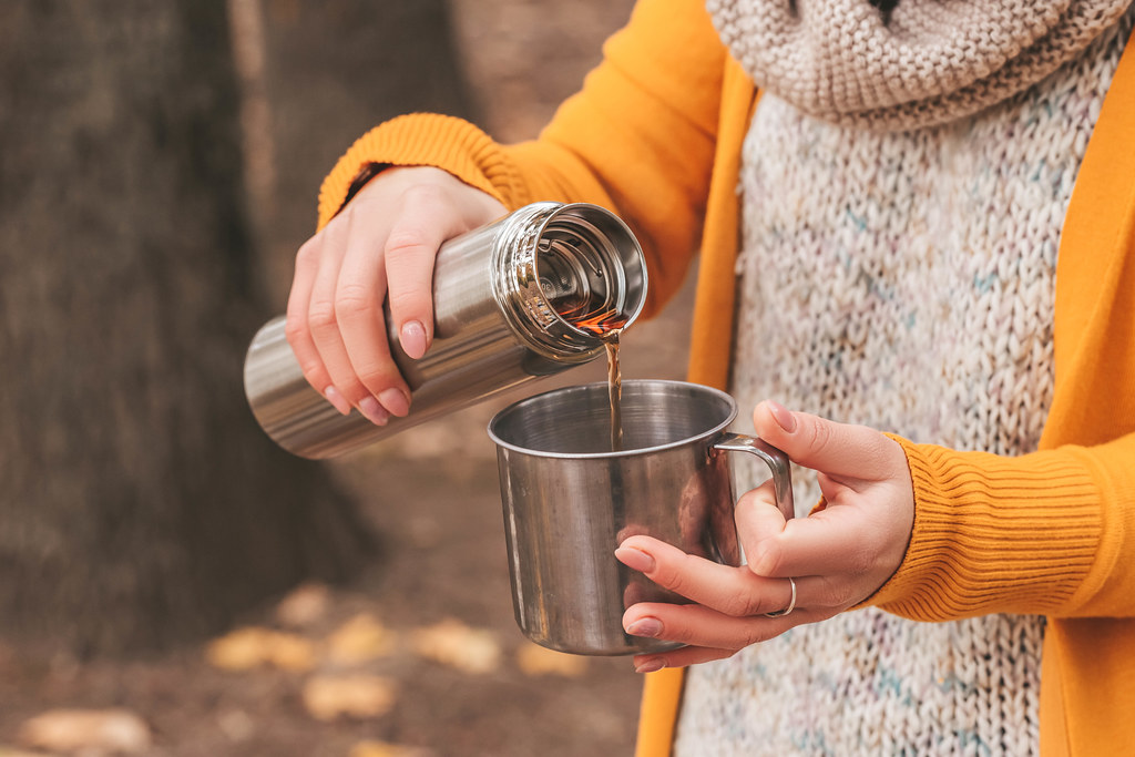 Hands of a girl pour tea from a thermos into a mug on an autumn background