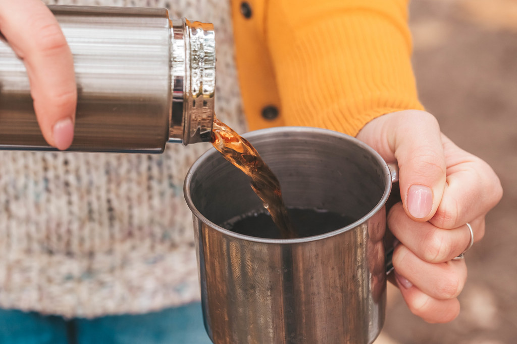 Close-up, pouring tea from a thermos into a mug