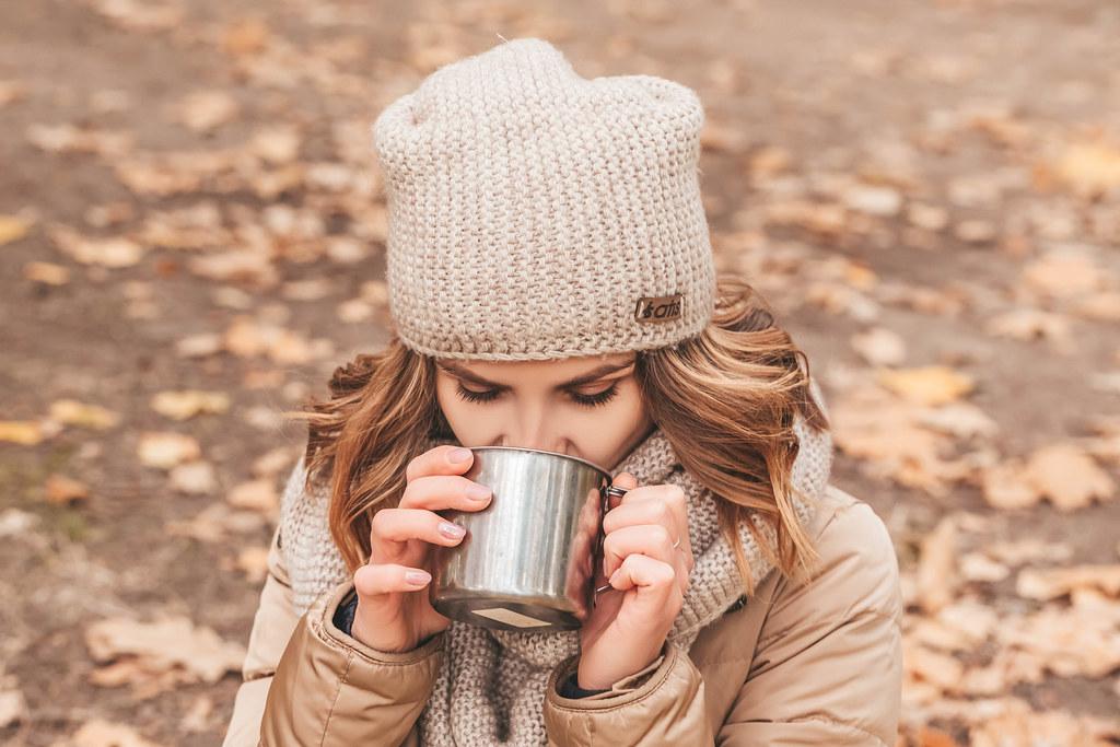 Woman in autumn park drinking tea from an iron mug