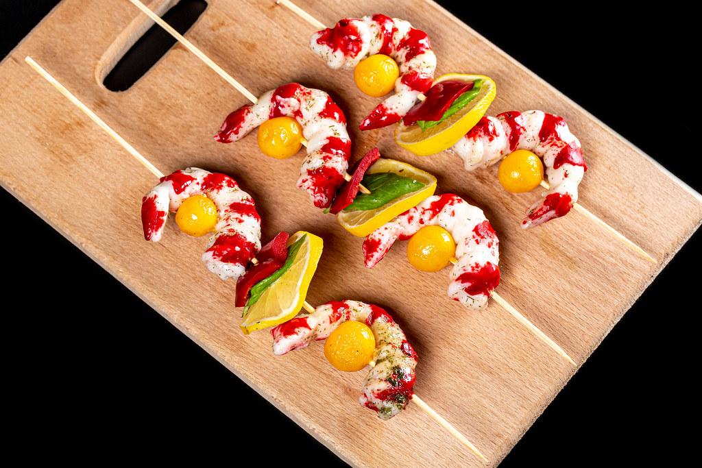 Fresh shrimp skewers on a wooden kitchen board