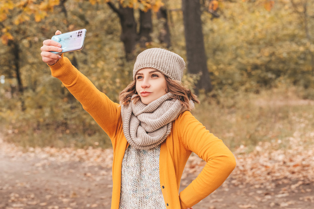 A girl is photographed in an autumn park on her mobile