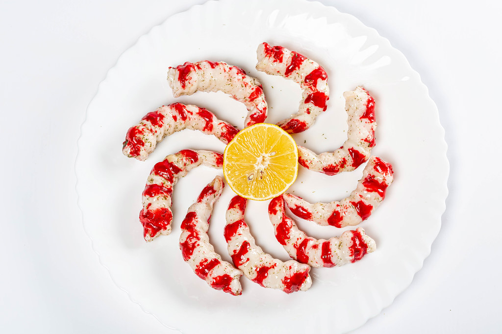 Large shrimp with lemon on a white plate, top view