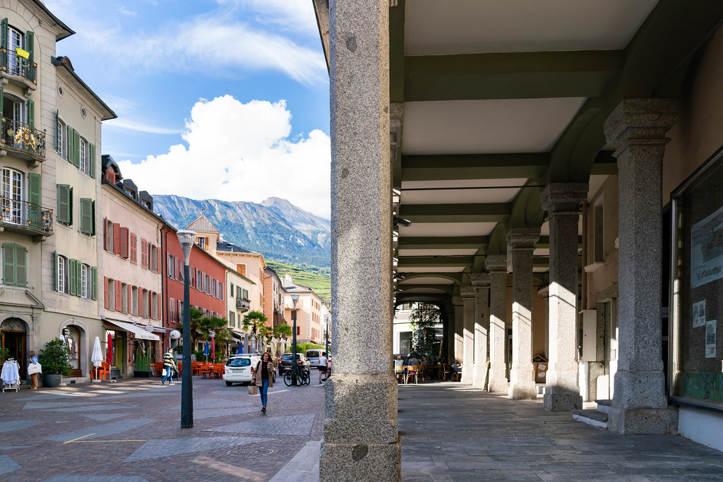 Overhanging passage on the right side and colorful Sion street with picturesque mountains on the left