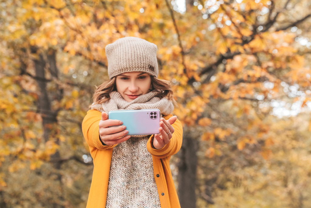 Girl with a smartphone in her hands in the autumn forest