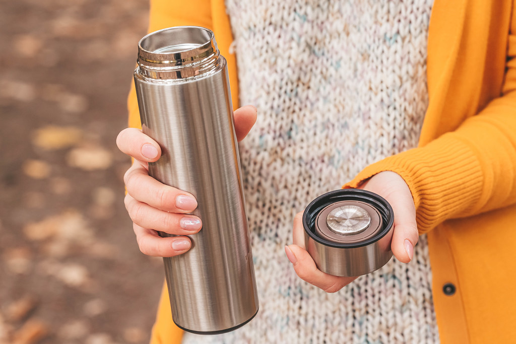 Girl holding an open thermos in her hands outdoors