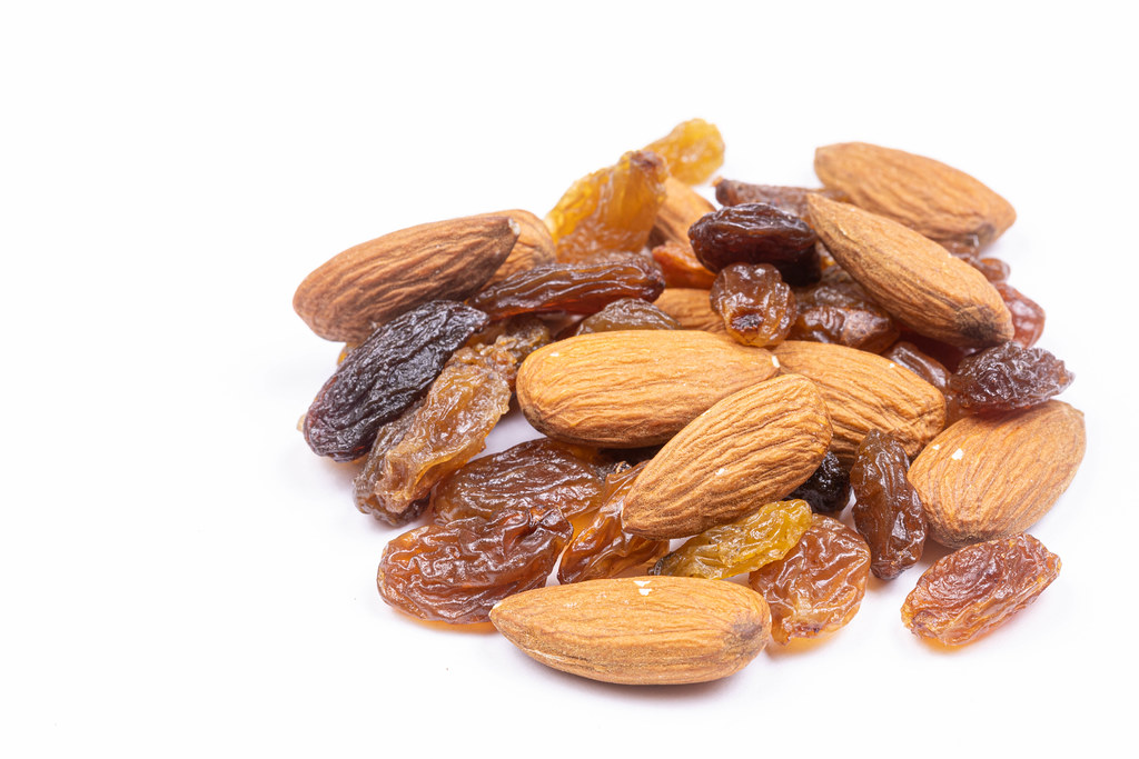 Pile of Raisins with Almonds above white background
