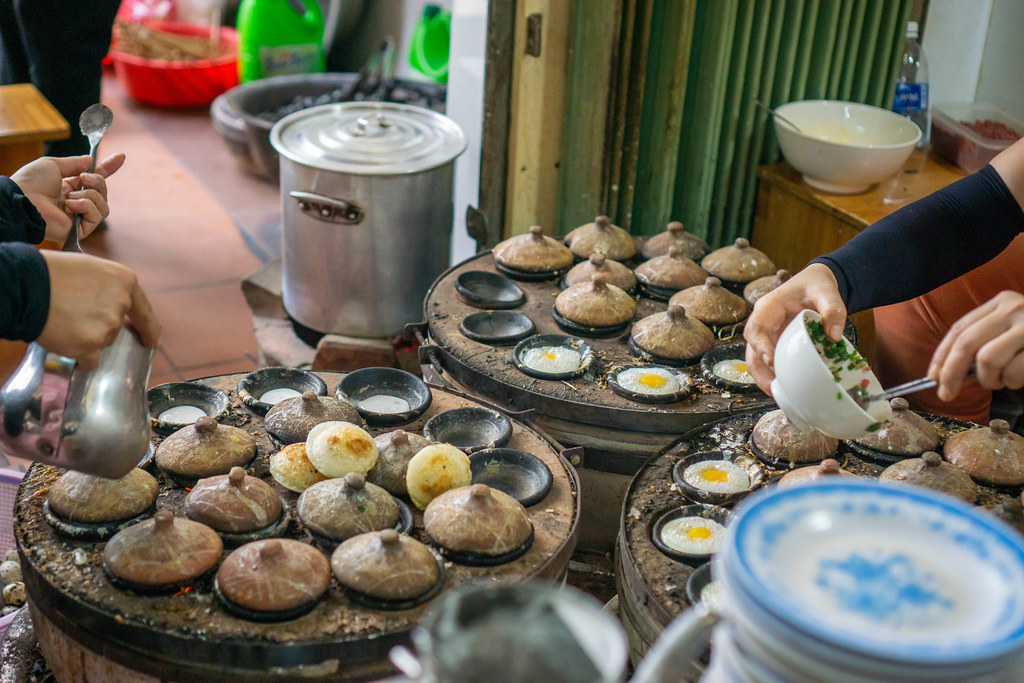 Two Women preparing Banh Can - Vietnamese Rice Cakes with a Traditional Stove in Da Lat, Vietnam