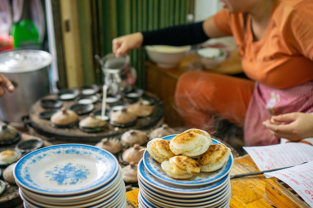Steaming Hot Banh Can - Vietnamese Rice Cakes on a Plate with Woman preparing more Cakes in the Background