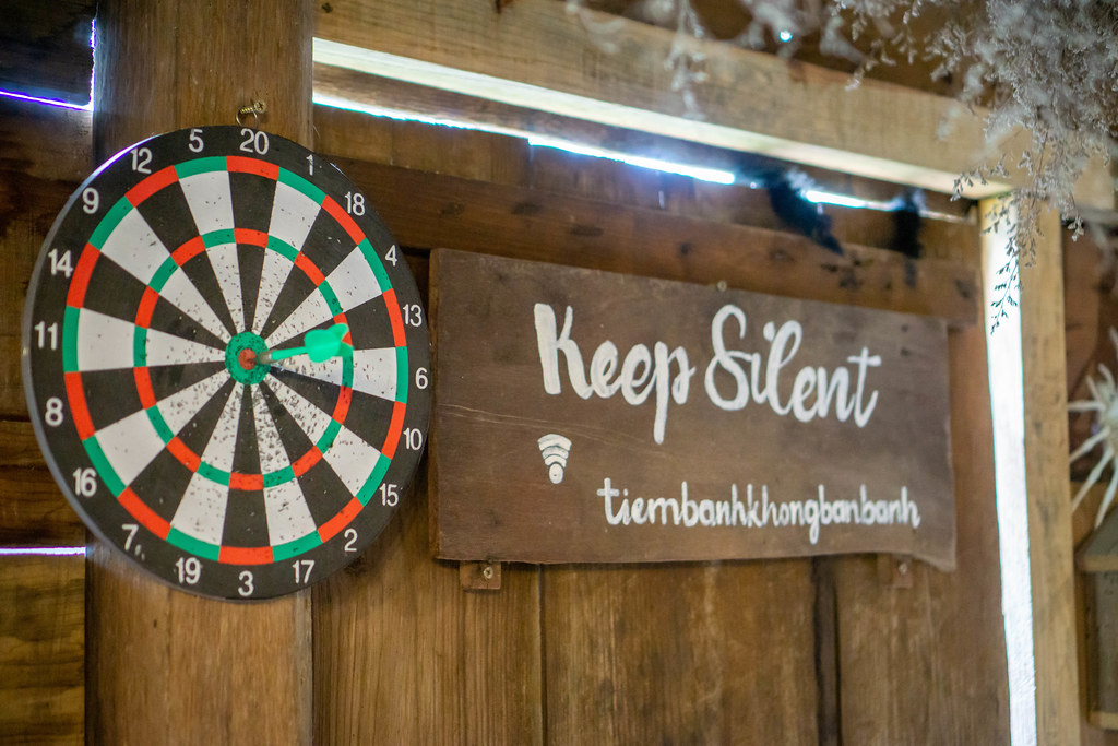 Wooden Board with Words Keep Silent and WiFi Password next to a Dart Board