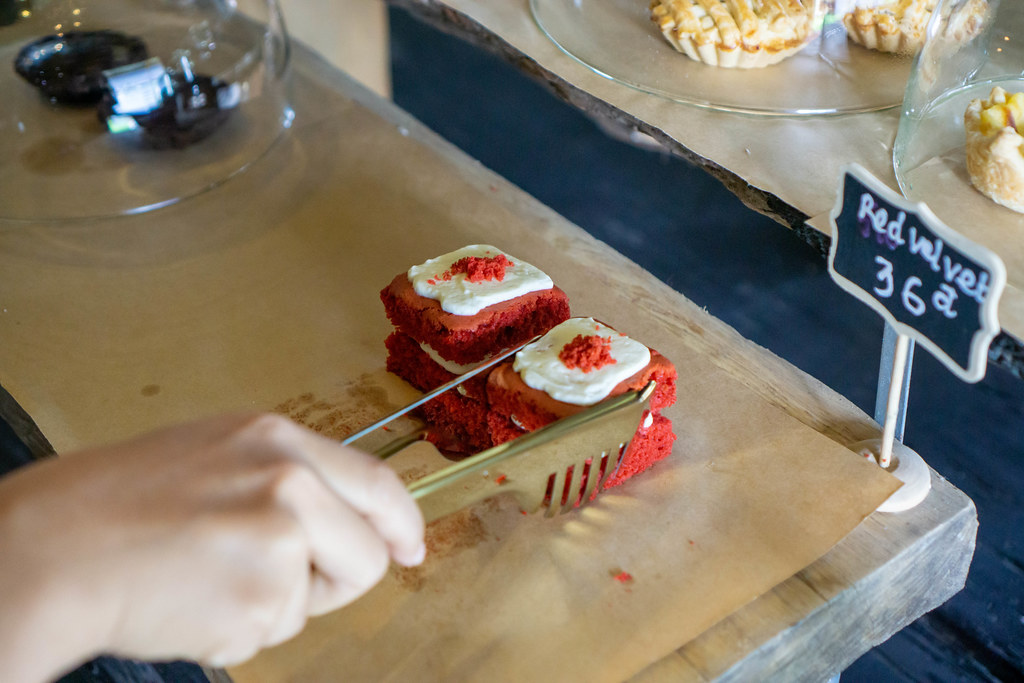 Person using Tongs to pick Red Velvet Cake in a Bakery