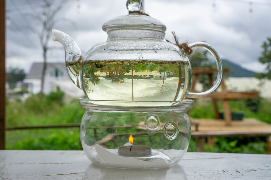 Close Up Photo of a Glass Tea Pot with Nature behind turned upside down