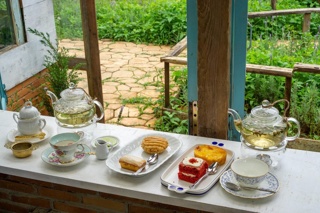 Glass Tea Pots, Tea Cups,  Plates and other Ceramics on a Wooden Windowsill facing a Garden