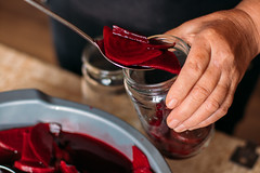 Person putting pickled beetroot slices in a transparent glass jar