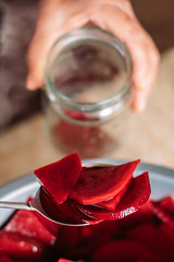 Person filling a transparent glass jar with sliced beetroot