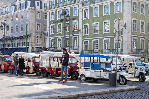 Lisbon, Portugal - January 17, 2020: Tuk Tuk drivers wait for passengers and tourists for taxi rides near Rossio Square