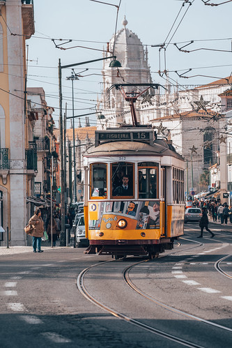 Lisbon, Portugal - January 17, 2020: An Iconic Lisbon (streetcar) tram moving along the streets in Belem, as the overhead cables decorated for Christmas