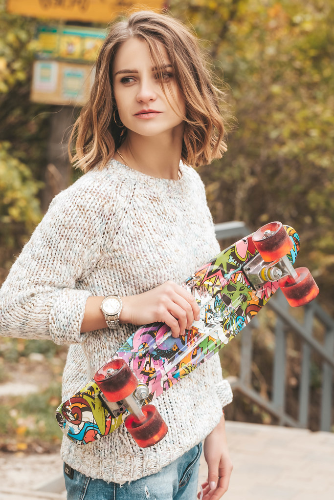 Close up of young attractive girl with skateboard standing outdoors and looking away