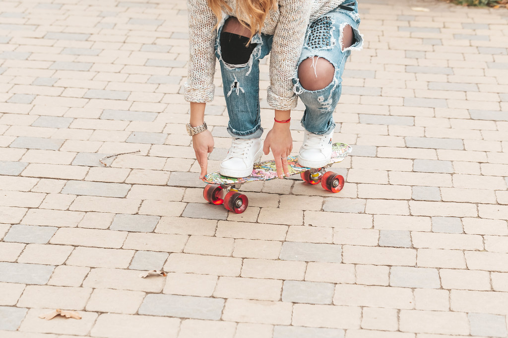 Young woman learning to skateboard