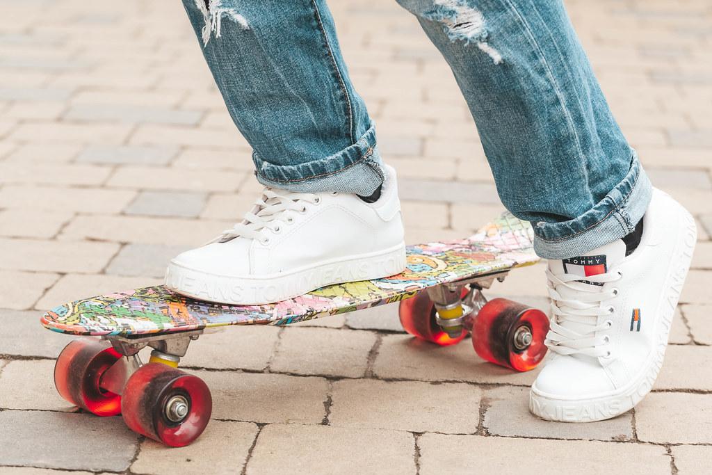 Girl in white sneakers on a skateboard