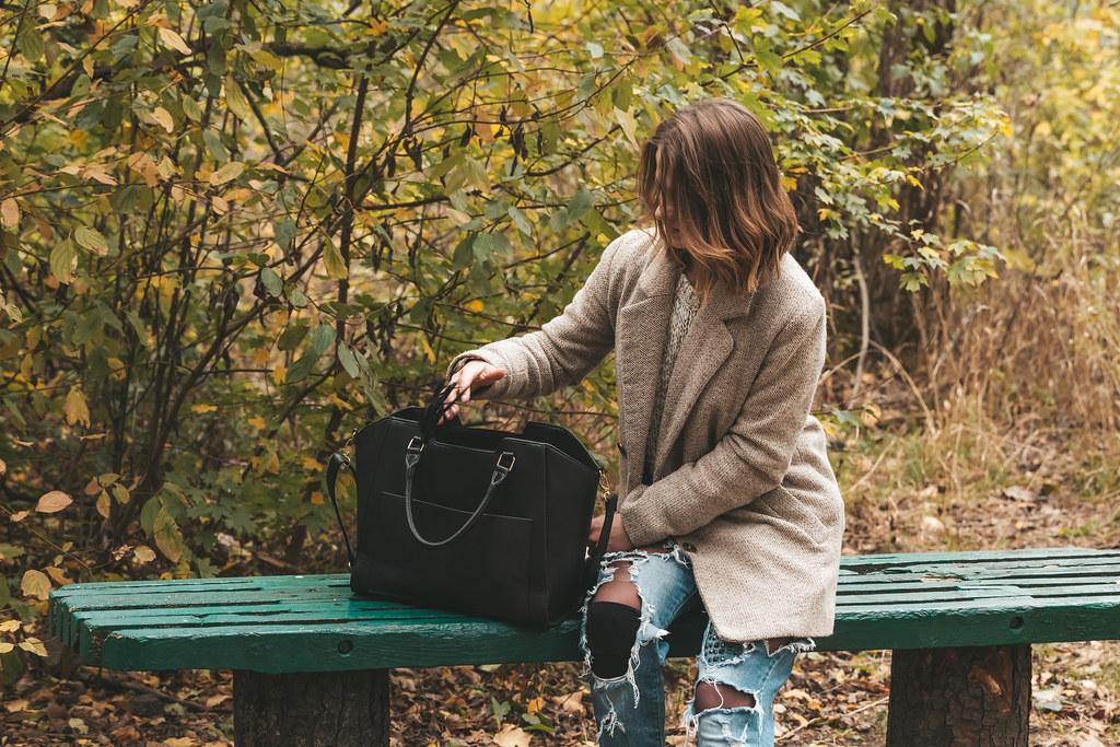 Young woman with black bag on a bench in the park