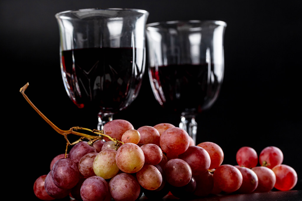Glasses of red wine with fresh grapes on a dark background