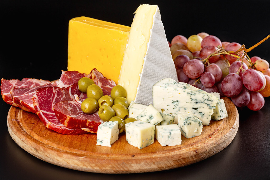 Wooden kitchen board with sliced delicatessen cheeses, ham, olives and grapes