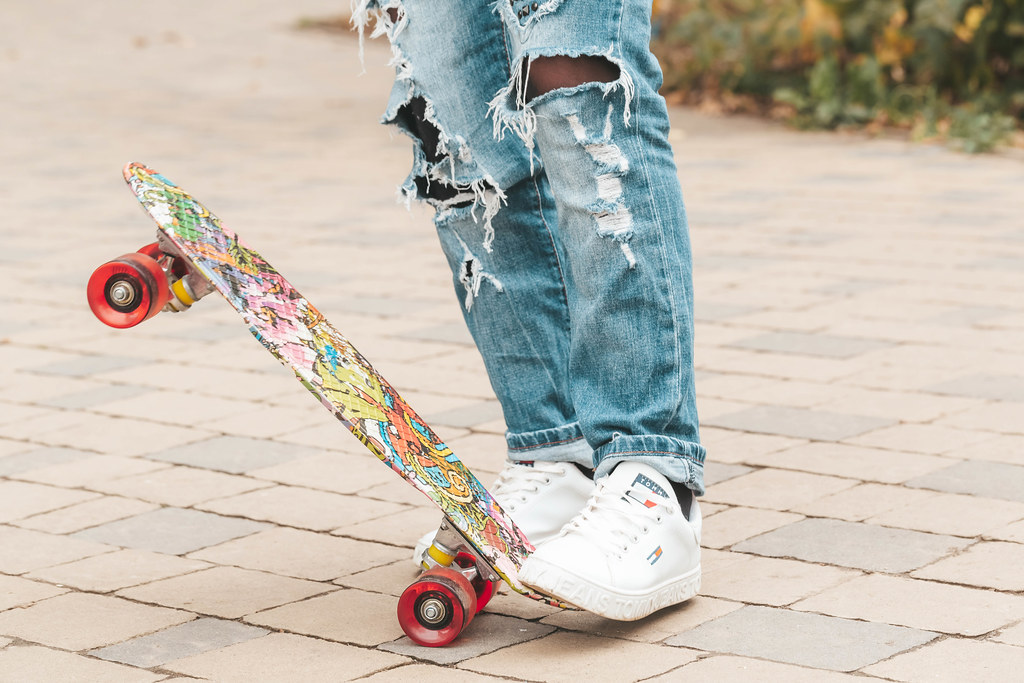 Legs of a girl in ripped jeans with a skateboard