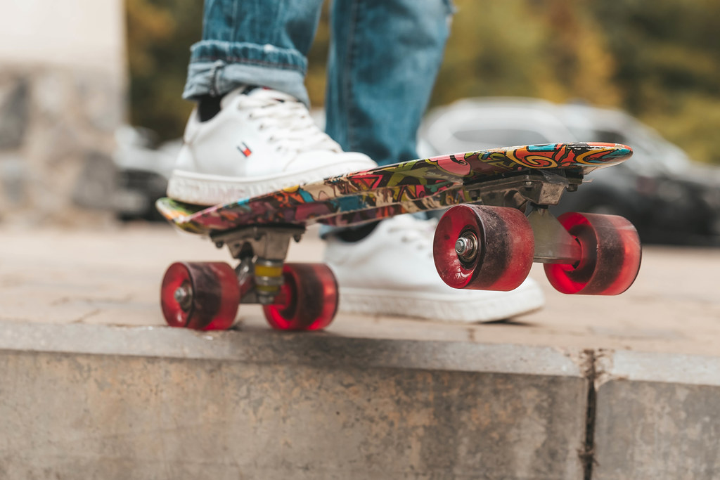 Close-up, legs of a girl and a skateboard on a blurred parking background