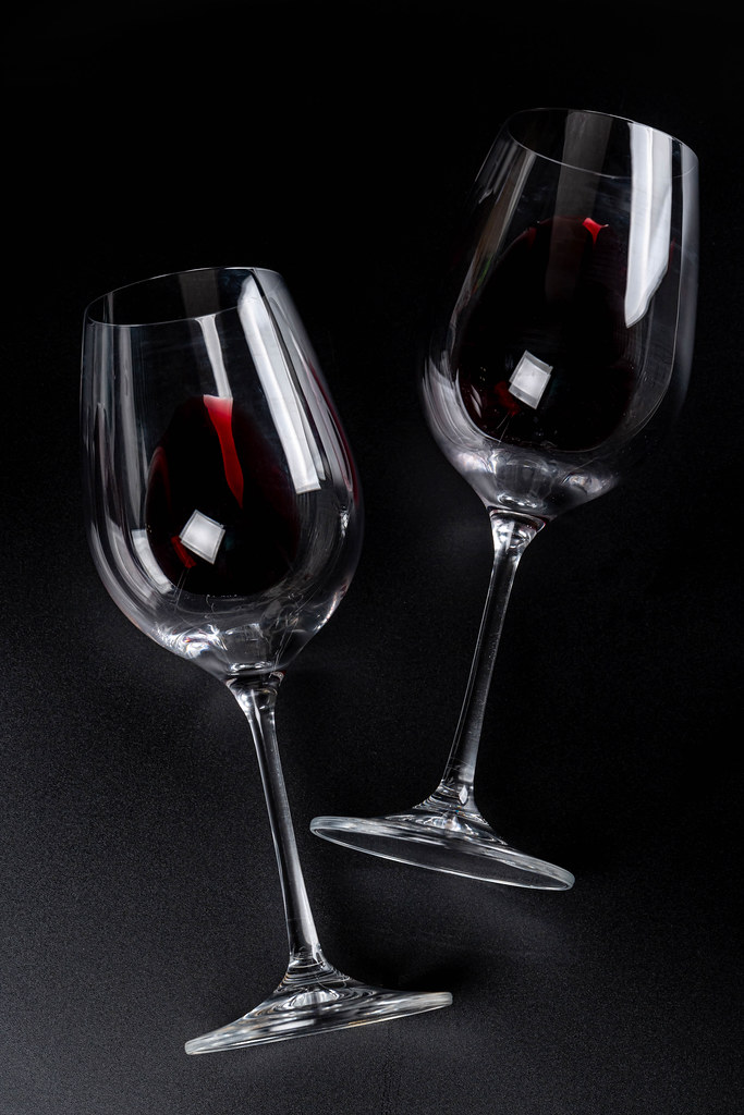 Two glasses with red wine on black background