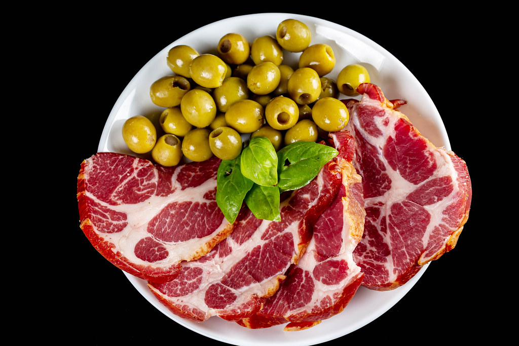 Plate with sliced smoked meat and green olives