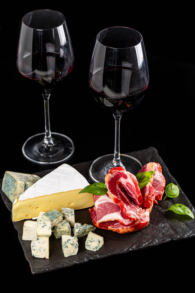 Delicious slicing of cheese and meat with red wine in glasses