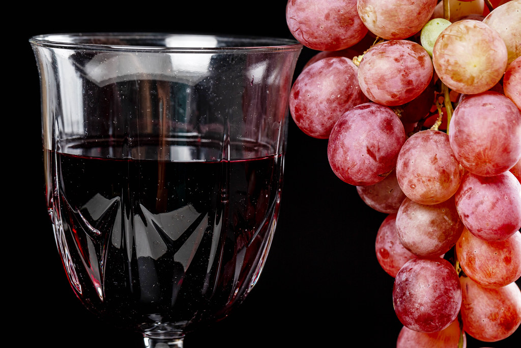 Close-up, red wine in a glass and fresh grapes