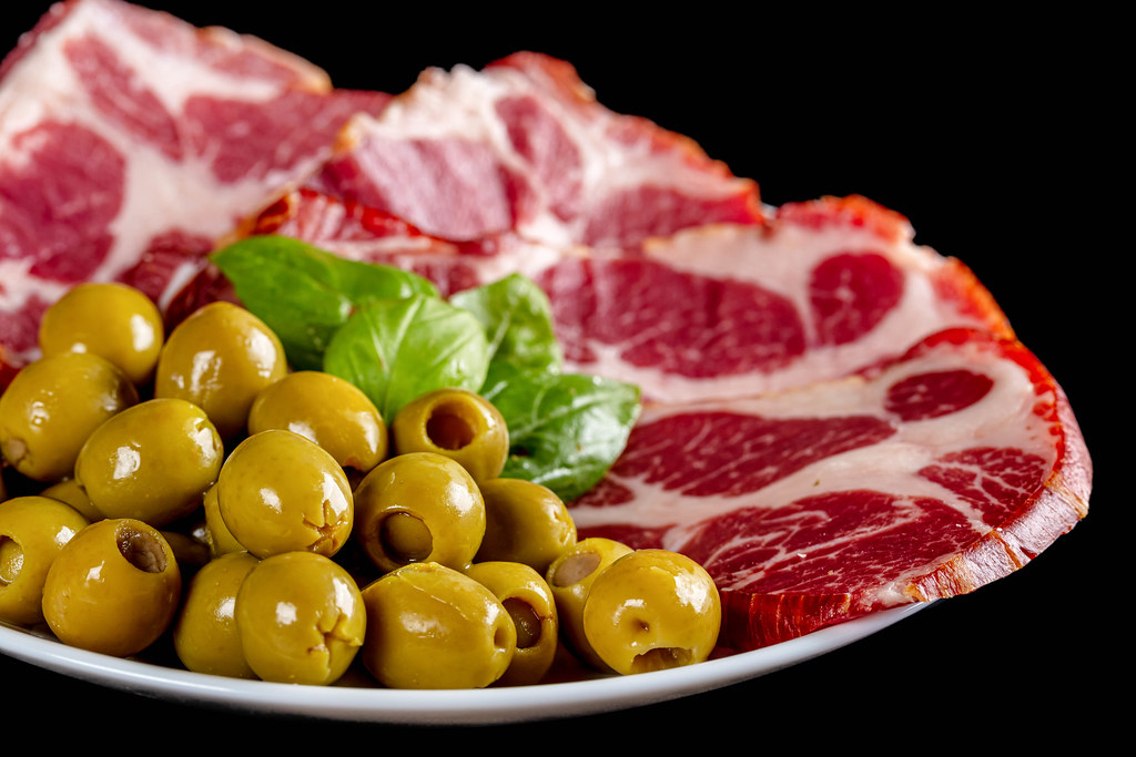 Green pickled pitted olives with sliced smoked meat